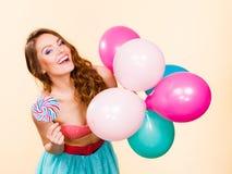 De vrouw houdt lollysuikergoed en ballons Royalty-vrije Stock Afbeelding