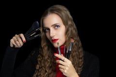 De vrouw houdt make-upborstels in haar handen royalty-vrije stock afbeeldingen
