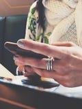 De vrouw houdt mobiele telefoon in haar hand royalty-vrije stock foto