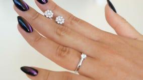 De vrouw houdt oorringen met diamanten tussen vingers en het bekijken op het haar handen dame die op één of ander juweel bij prob stock video