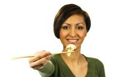 De vrouw houdt stuk van bloemkool met eetstokjes royalty-vrije stock afbeelding