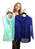 De vrouw houdt twee blouses en kan niet voor haar kiezen Stock Afbeeldingen