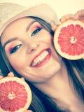 De vrouw houdt twee halfs van grapefruitcitrusvruchten in handen Royalty-vrije Stock Afbeeldingen