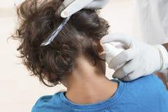 De vrouw inspecteert childs hoofd van schoolkind voor luizen Stock Foto