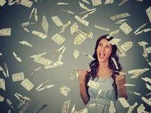 De vrouw jubelt pompende extatische vuisten viert succes onder geldregen die onderaan de bankbiljetten van dollarrekeningen valle Stock Foto's