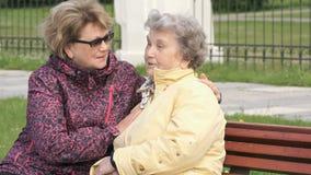 De vrouw kalmeert oude vrouw in openlucht tijdens spanning stock video