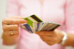 De vrouw kiest één creditcard van velen, concept creditcard royalty-vrije stock afbeelding
