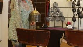 De vrouw kiest decoratieve toebehoren in de opslag stock videobeelden