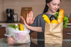 De vrouw kiest een document zak met voedsel en weigert om plastiek te gebruiken Concept milieubescherming royalty-vrije stock afbeelding
