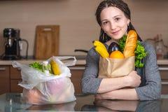De vrouw kiest een document zak met voedsel en weigert om plastiek te gebruiken Concept milieubescherming stock afbeelding