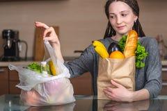 De vrouw kiest een document zak met voedsel en weigert om plastiek te gebruiken Concept milieubescherming royalty-vrije stock foto's