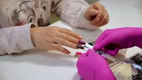 De vrouw kiest een kleur voor het schilderen van spijkers in een schoonheidssalon Een inzameling van nagellakmeetapparaten in div stock video