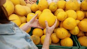 De vrouw kiest fruit in supermarkt Een jong meisje koopt voedsel voor een veganistdieet Gezond voedsel, heldere gele groenten bin stock videobeelden