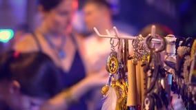 De vrouw kiest juwelen bij een nachtmarkt Een markt in het licht van avondlampen stock video