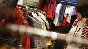 De vrouw kiest Kleren die Kostuums in Boutique sorteren stock footage
