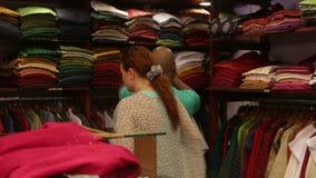 De vrouw kiest kleren in een winkel stock videobeelden