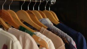De vrouw kiest kleren in de garderobe stock video