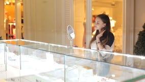 De vrouw kiest oorringen in een juwelenopslag stock footage
