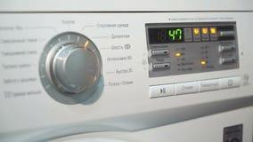 De vrouw kiest programmacyclus op een wasmachine