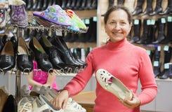 De vrouw kiest schoenen bij schoenenwinkel royalty-vrije stock fotografie