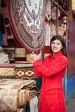 De vrouw kiest tapijt Stock Foto