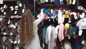 De vrouw kiest textiel in gordijn die, die en het raken onderzoeken stock videobeelden