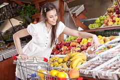 De vrouw kiest voedsel in supermarkt Royalty-vrije Stock Foto's
