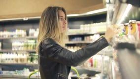 De vrouw kiest yoghurt in de supermarkt Blondevrouw die producten in winkelcomplex kiezen Het meisje bevindt zich dichtbij de ops stock footage