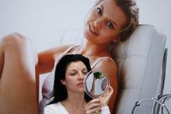 De vrouw kijkt in de spiegel Royalty-vrije Stock Afbeeldingen
