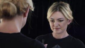 De vrouw kijkt in de spiegel en past haar wenkbrauwenpincet aan Sluit omhoog stock video