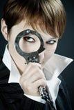 De vrouw kijkt door handcuff als vergrootglas stock foto's