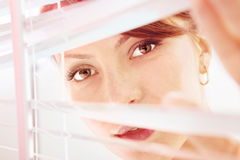 De vrouw kijkt door jaloezie sm Royalty-vrije Stock Foto's