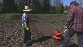De vrouw kijkt hoe man die grond cultiveren stock footage