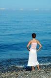 De vrouw kijkt op zee Stock Fotografie