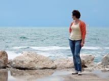 De vrouw kijkt op zee stock afbeelding