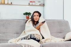De vrouw kijkt TV op de laag De mooie vrouw die op TV letten viel in slaap stock fotografie
