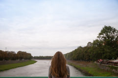De vrouw kijkt uit over het vage rivierlandschap Stock Fotografie