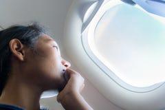 De vrouw kijkt uit van vliegtuig Royalty-vrije Stock Fotografie