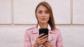 De vrouw kijkt verbaasd na gelezen bericht in smartphone stock footage