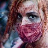 De vrouw kleedde zich aangezien een zombie op een straat tijdens een zombiegang paradeert Stock Afbeeldingen