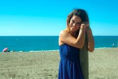 De vrouw kleedde zich in blauw op het strand Stock Foto