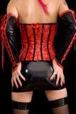 De vrouw kleedde zich in dominatrixkleren, van rug Stock Foto