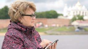 De vrouw kleedde zich in sportjasje houdend mobiele telefoon stock video
