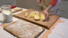 De vrouw kneedt het deeg en het knipsel het in plakken Voorbereiding van bollen, traditionele Oekraïense keuken stock videobeelden