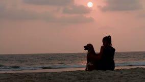 De vrouw koestert haar hond bij zonsondergang