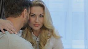 De vrouw koestert thuis haar echtgenoot stock videobeelden