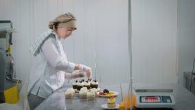 De vrouw kookt cakes voor een vakantie Bij het meisje is de orde als snoepwinkel kleine onderneming De cakes zijn klaar op a stock videobeelden