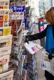 De vrouw koopt een Franse de Perskrant van Le Monde van een newssta royalty-vrije stock afbeelding