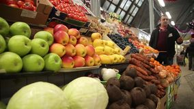 De vrouw koopt groenten bij een landbouwbedrijfmarkt stock videobeelden