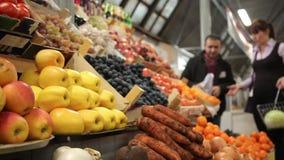 De vrouw koopt groenten bij een landbouwbedrijfmarkt showcase stock videobeelden